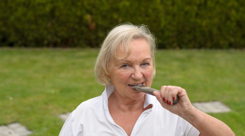 Attraktive Rentnerin mit Eisenl zwischen den Zähnen